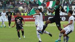 Indosport - Amido Balde berebut bola dengan pemain Madura united.