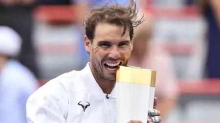 Rafael Nadal menggigit piala yang baru diraih olehnya usai kalahkan Daniil Medvedev. - INDOSPORT
