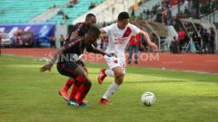 Indosport - Reva Adi Utama (putih) berusaha melewati dua pemain Persipura Jayapura.