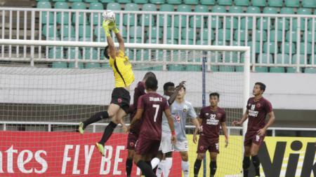 Kiper PSM Makassar, Rivky Mokodompit (kuning), menangkap bola di udara saat melawan Kaya FC pada penyisihan grup Piala AFC 2019 di Stadion Pakansari, Bogor. - INDOSPORT