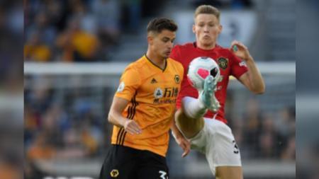 Scott McTominay berusaha menjaga bola dari lawan di pertandingan Liga Primer Inggris antara Wolverhampton vs Manchester United - INDOSPORT