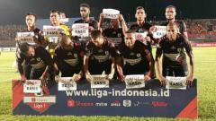 Indosport - Skuat Persipura Jayapura saat membentangkan kertas bertuliskan pesan penolakan terhadap rasisme