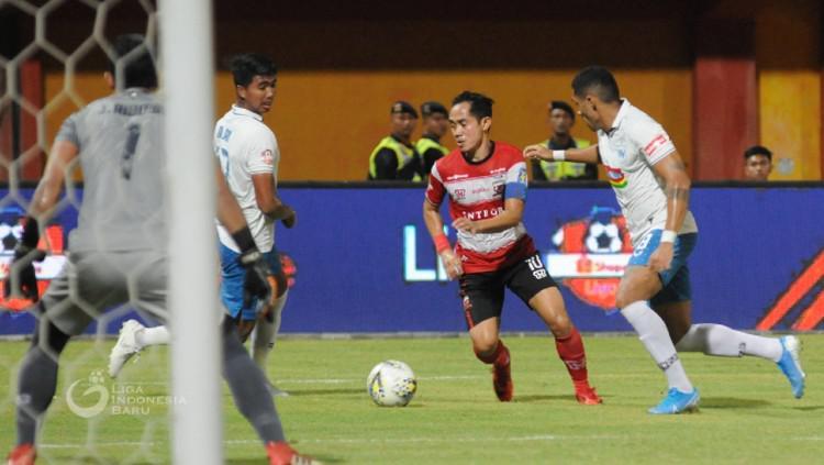 Slamet Nurcahyo berusaha melewati Patrick Mota dalam pertandingan Liga 1 2019 Madura United vs PSIS Semarang, Sabtu (24/08/19) malam. Copyright: liga-indonesia.id