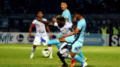 Indosport - Hambali Tolib berusaha berebut bola dengan Louise Parfait pada pertandingan Liga 1 2019 antara Persela Lamongan vs TIRA Persikabo, Minggu (25/08/19)