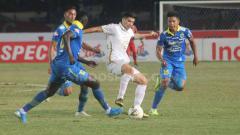 Indosport - Satu pemain PSS Sleman berusaha melewati tiga pemain Persib Bandung sekaligus.