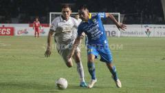 Indosport - Gelandang Persib, Omid Nazari berduel dengan pemain PSS Sleman, Guilherme Batata.