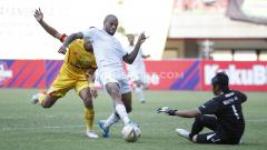 Indosport - Striker Persebaya David da Silva (tengah) saat mengecoh kiper Bhayangkara FC.