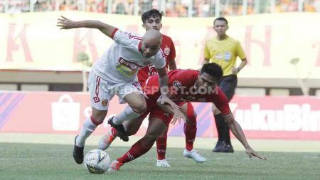 Bek Persija Jakarta, Fachrudin Aryanto duel dengan pemain Badak Lampung di stadion Patriot, Bekasi. - INDOSPORT