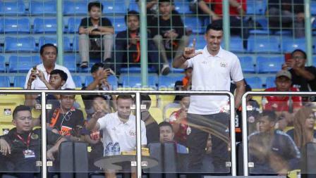Alexandre Reame Xandao tengah berdiri memberikan simbol Jakmania di tribun dalam laga Persija Jakarta vs Perseru Badak Lampung.