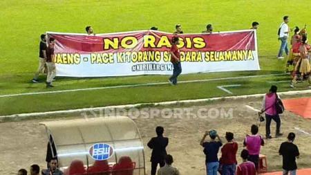 Perwakilan dari seluruh kelompok suporter PSM Makassar mengibarkan spanduk anti rasisme di laga melawan Persela Lamongan. - INDOSPORT