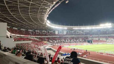 Suporter Timnas Indonesia membuat mozaik yang membentuk tulisan. - INDOSPORT