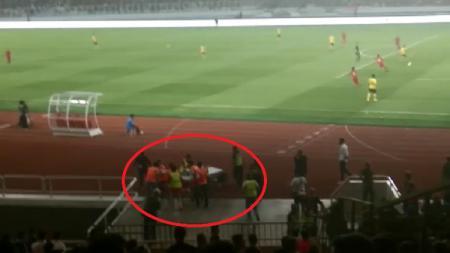 Seorang terduga suporter Malaysia harus ditandu oleh medis usai jadi korban kericuhan di dalam stadion pada laga Timnas Indonesia vs Malaysia, Kamis (05/09/19). - INDOSPORT