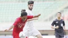 Indosport - Pemain Timnas U-19, Fajar Fathur Rachman (kiri) berusaha amankan bola dari pemain Iran pada laga uji coba.