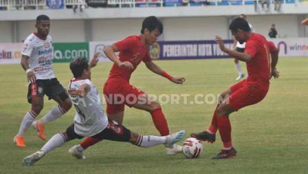 Winger Timnas U-22, Feby Eka Putra berusaha melewati tekel pemain Bali United, yang ingin merebut bola darinya.