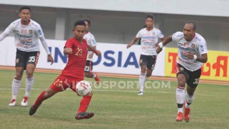Sani Rizki berusahan menendang bola yang dikelilingi oleh para pemain Bali United.