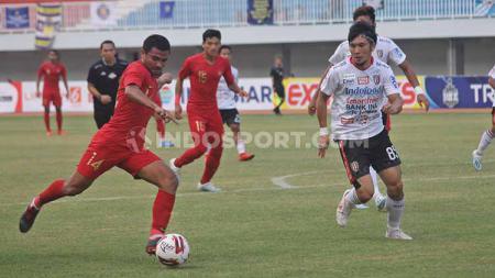 Bek Timnas U-22, Asnawi Mangkualam (kiri) berusaha melewati bek Bali United, Michael Orah dalam laga Trofeo HB X di Stadion Mandala Krida, Yogyakarta, Minggu (08/09/19). - INDOSPORT