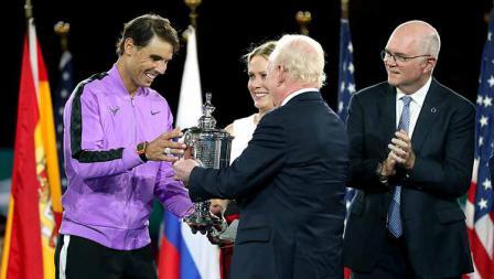 Rafael Nadal menerima trofi AS Terbuka 2019 dari legenda tenis, Rod Laver.