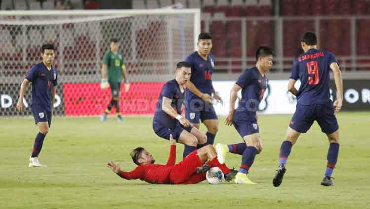 Stefano Lilipaly (bawah), terjatuh berjibaku untuk menguasai bola di tengah pengawalan para pemain Thailand, Selasa (10/09/2019). Foto: Herry Ibrahim/INDOSPORT. Copyright: Herry Ibrahim/INDOSPORT