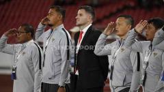 Indosport - Simon McMenemy (tengah) bersama tim pelatih Timnas Indonesia di pinggir lapangan saat lagu kebangsaan Indonesia Raya dinyanyikan, Selasa (10/09/2019).