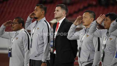 Simon McMenemy (tengah) bersama tim pelatih Timnas Indonesia di pinggir lapangan saat lagu kebangsaan Indonesia Raya dinyanyikan, Selasa (10/09/2019). - INDOSPORT