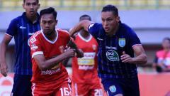 Indosport - Bomber Persela, Alex Dos Santos (kanan), berebut bola dengan pemain Badak Lampung dalam laga pekan ke-17 Liga 1 2019, Rabu (11/09/19).