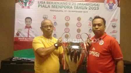 Kabid Olahraga Pendidikan Deputi Kebudayaan Olahraga Kemenpora Ari Mulyadi (kiri) memamerkan Piala Menpora U-21. - INDOSPORT
