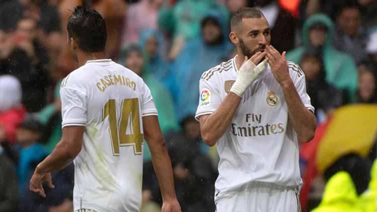 Selebrasi pemain Real Madrid, Karim Benzema usai mencetak gol ke gawang Levante di stadion Santiago Bernabeu, Sabtu (14/09/19). Copyright: CURTO DE LA TORRE/AFP/Getty Images