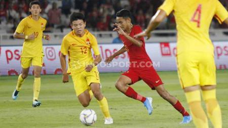 Gelandang Timnas Indonesia U-16, Marselino Ferdinan (kanan) menggiring bola dan dalam penjagaan Xu Bin, Minggu (22/09/2019). Foto: Herry Ibrahim/INDOSPORT. - INDOSPORT