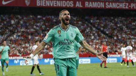 Striker Real Madrid, Karim Benzema, merayakan golnya ke gawang Sevilla dalam lanjutan Liga Spanyol 2019/20. - INDOSPORT