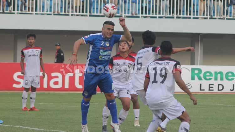 Cristian Gonzales mengambil bola atas dari pemain Madura FC. Copyright: Ronald Seger Prabowo/INDOSPORT