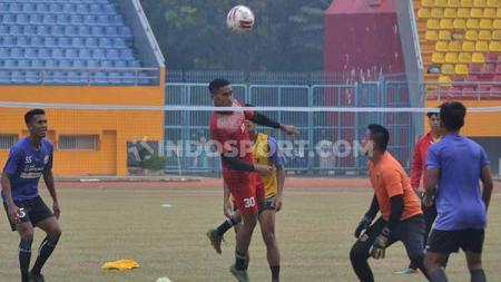 Kiper Sriwijaya FC, Hendra Mole, menyundul bola saat latihan takraw. - INDOSPORT