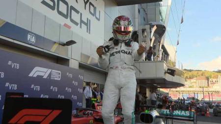 Lewis Hamilton melakukan selebrasi diatas mobilnya usai finish - INDOSPORT