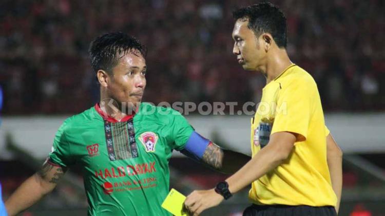 Kapten Kalteng Putra, Gede Sukadana saat berdiskusi dengan wasit Yudi Nurcahya asal Jawa Barat. Copyright: Nofik Lukman Hakim/INDOSPORT