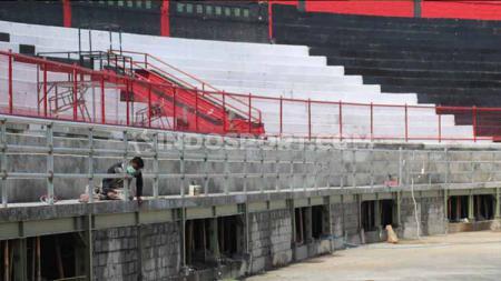 Salah seorang pekerja tampak sedang melakukan pengerjaan tribun sisi utara di Stadion Kapten I Wayan Dipta Gianyar - INDOSPORT