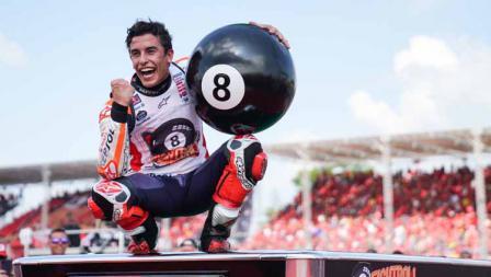 Marc Marquez membawa bola dan duduk diatas meja billiar.