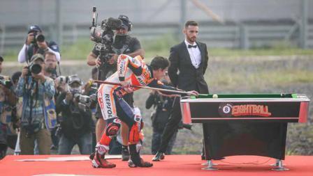 Aksi Marc Marquez berusaha memasukan bola billiar usai dinobatkan menjadi juara MotoGP 2019.