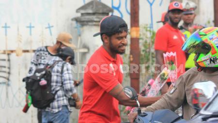 Gelandang andalan Persipura, Imanuel Wanggai saat membagikan bunga kepada warga pengguna jalan. - INDOSPORT