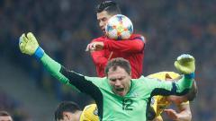 Indosport - Cristiano Ronaldo saat berusaha berduel di udara dengan para pemain Ukraina.