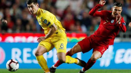 Cristiano Ronaldo saat berebut bola dengan pemain Ukraina. - INDOSPORT