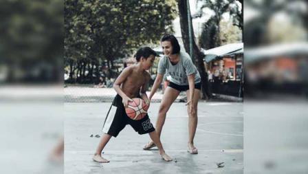 Wanda Hamidah tengah bermain bola basket bersama putranya.