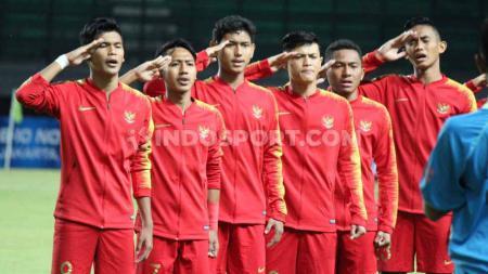 Para pemain Timnas Indonesia U-19 serempak melakukan gerakan hormat kala lagu kebangsaan Indonesia Raya berkumandang. - INDOSPORT