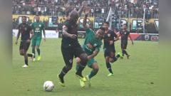 Indosport - Penyerang PSS Sleman, Antoni Putro Nugroho (kanan) berusaha melewati adangan bek Kalteng Putra, OK John dalam laga Liga 1 di Stadion Maguwoharjo, Jumat (18/10/19).