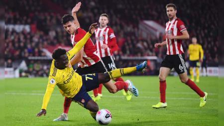 Bukayo Saka dijatuhkan pemain lawan pada laga Sheffield United vs Arsenal di Liga Inggris (Premier League) 2019/2020, Selasa (22/10/19). - INDOSPORT