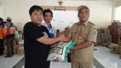Indosport - Sudarmaji mewakili Arema FC memberikan bantuan.