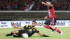 Indosport - Bek Barito Putera, Cassio De Jesus berusaha membuang bola yang hendak direbut gelandang Bali United, Paulo Sergio dalam lanjutan Shopee Liga 1 2019 di Stadion Kapten I Wayan Dipta, Gianyar, Minggu (27/10/19).