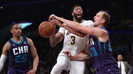 Pemain bintang LA Lakers, Anthony Davis (tengah) mendapat penjagaan ketat dari pemain Charlotte Hornets, Cody Zellers dalam pertandingan ketiga NBA 2019-2020 - INDOSPORT