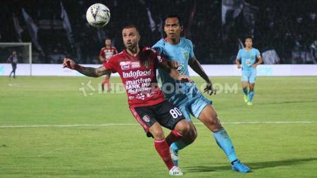 Gelandang Persela Lamongan, Lucky Wahyu mengawal ketat pergerakan gelandang Bali United, Paulo Sergio dalam laga pekan ke-26 Shopee Liga 1 2019 di Stadion Kapten I Wayan Dipta, Gianyar, Kamis (31/10/19). - INDOSPORT