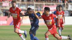 Indosport - Dua pemain Badak Lampung FC tengan berduel dengan Ricky Kayame