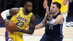 Indosport - Point guard LA Lakers, LeBron James (kiri) mendapat penjagaan ketat dari Small Forward Dallas Mavericks, Luka Doncic dalam pertandingan NBA Musim Reguler 2019-2020