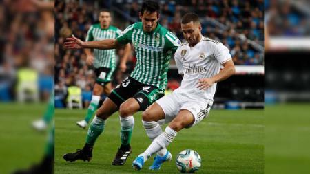 Eden Hazard (kanan) dikawal pemain lawan pada laga Real Madrid vs Real Betis di LaLiga 2019/2020, Minggu (03/11/19). - INDOSPORT